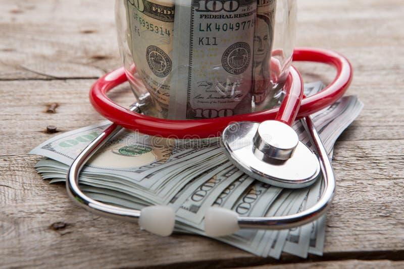 ziektekostenverzekeringconcept - stethoscoop over het geld stock afbeelding