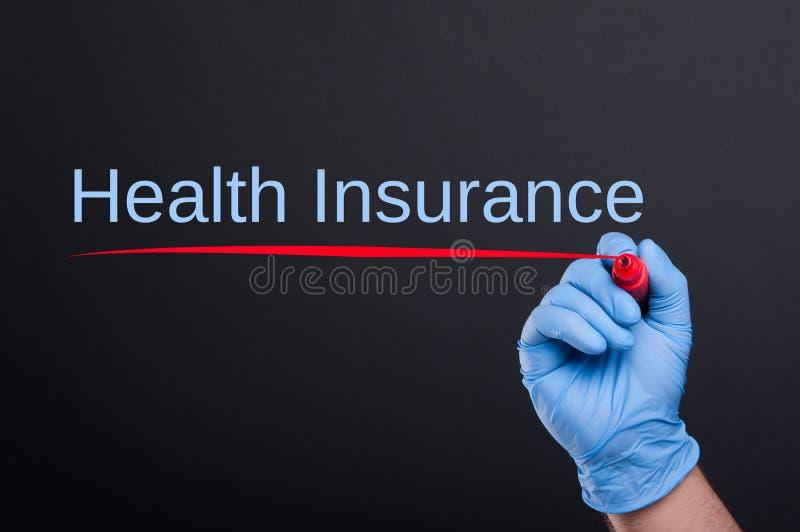 Ziektekostenverzekeringtekst door artsenhand die wordt geschreven royalty-vrije stock fotografie