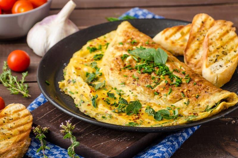 Zielarski omelette z szczypiorkami i oregano kropiącymi z Zielarskim omelette z chili płatkami zdjęcia stock