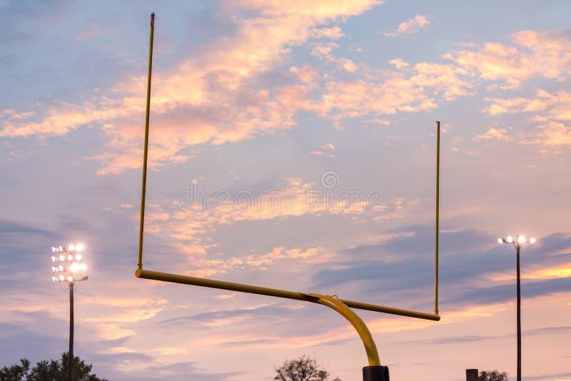 Zielbeiträge des amerikanischen Fußballs gegen Sonnenuntergang stockfotografie