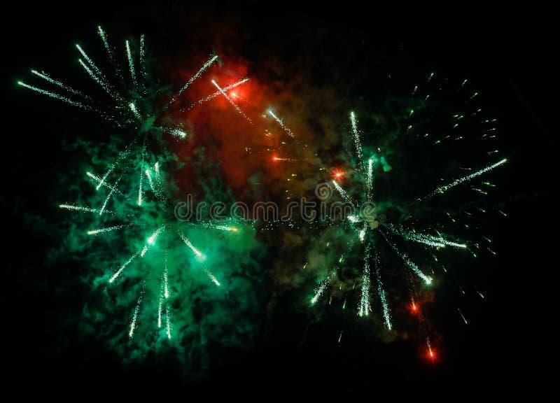 Zieleń, czerwony salut i fajerwerki z czarnym nieba tłem obrazy royalty free