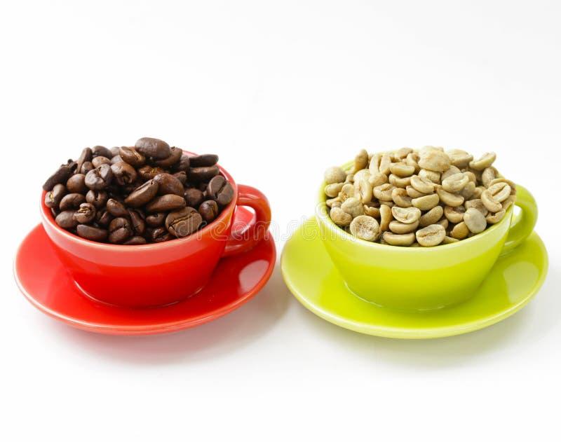 Zieleń i czarne kawowe fasole w filiżance fotografia royalty free