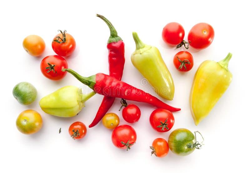 Zieleń i dojrzali czereśniowi pomidory, dzwonkowi pieprze, chili na bielu obraz royalty free