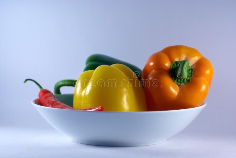 Zieleń, kolor żółty, pomarańcze i czerwony pieprz na białym talerzu, fotografia royalty free