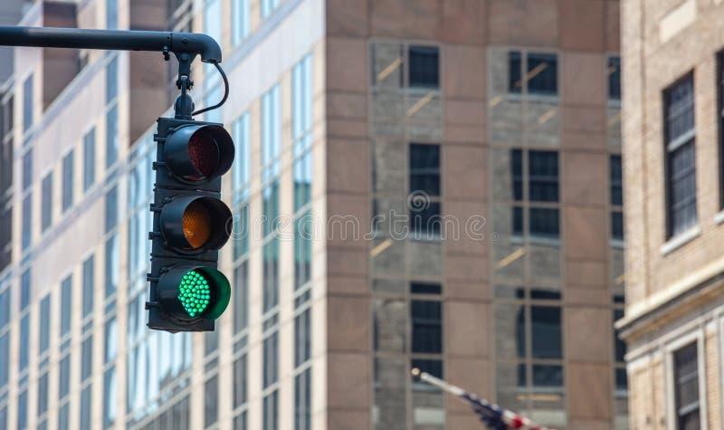 Zieleni światła ruchu dla samochodów, plama budynków biurowych tło fotografia royalty free