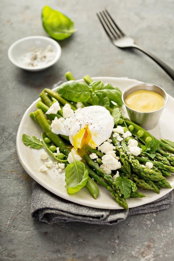 Zieleni grochy i asparagus z kłusującym jajkiem fotografia stock