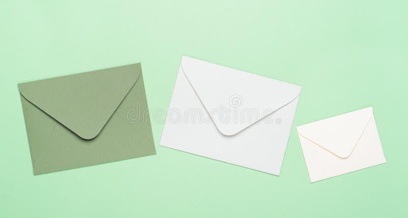 Zieleni i bielu koperty na zielonym tle Pojęcie listy, wiadomości, korespondencja, kopii przestrzeń, odgórny widok zdjęcia royalty free