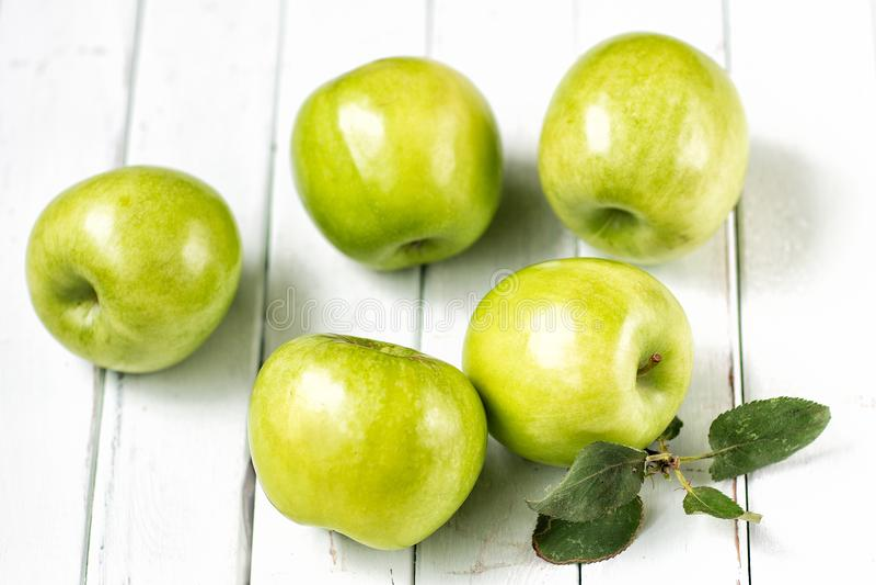 Zieleni jabłka na lekkim drewnianym tle zdjęcia stock