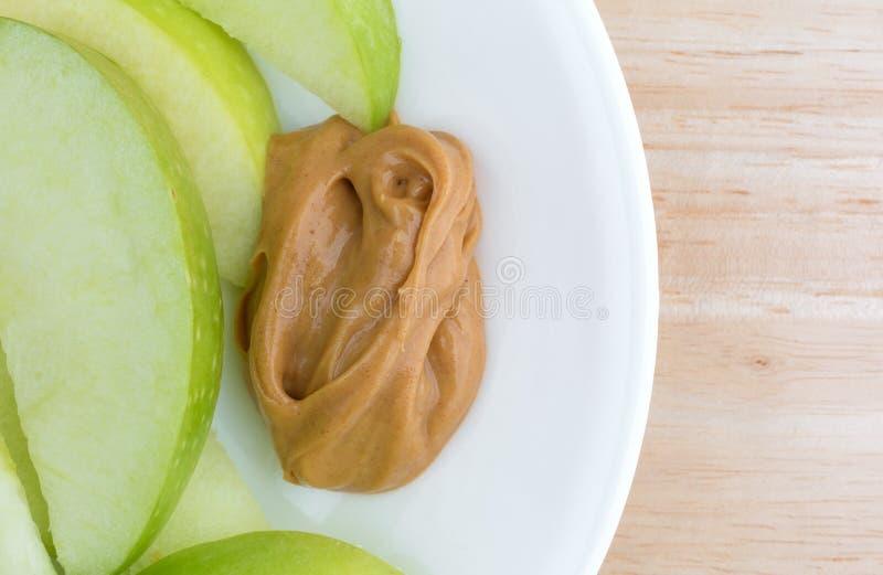 Zieleni jabłko plasterki na naczyniu z masło orzechowe stołowym wierzchołkiem obraz stock