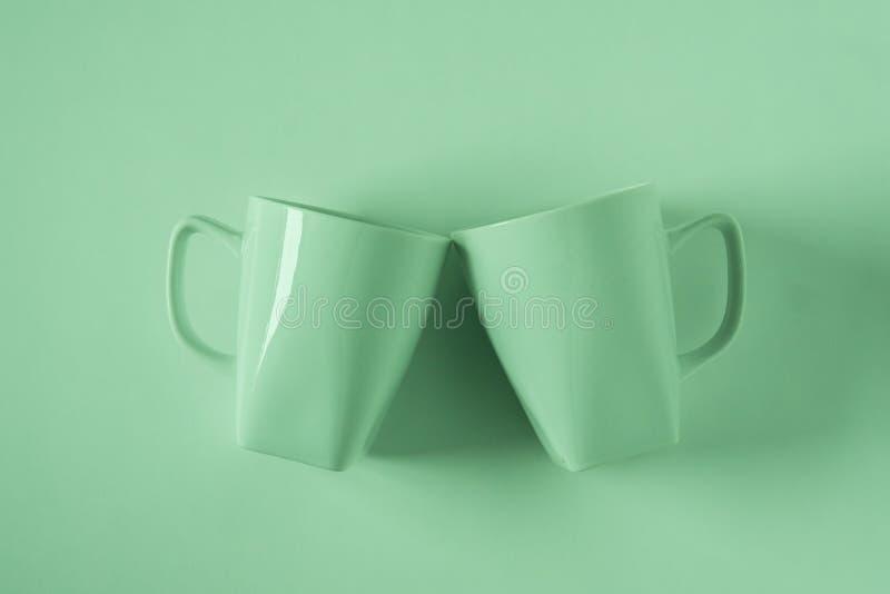 Zieleni kawowi kubki na zielonym tle clinking w otuchach z pustym copyspace obraz stock