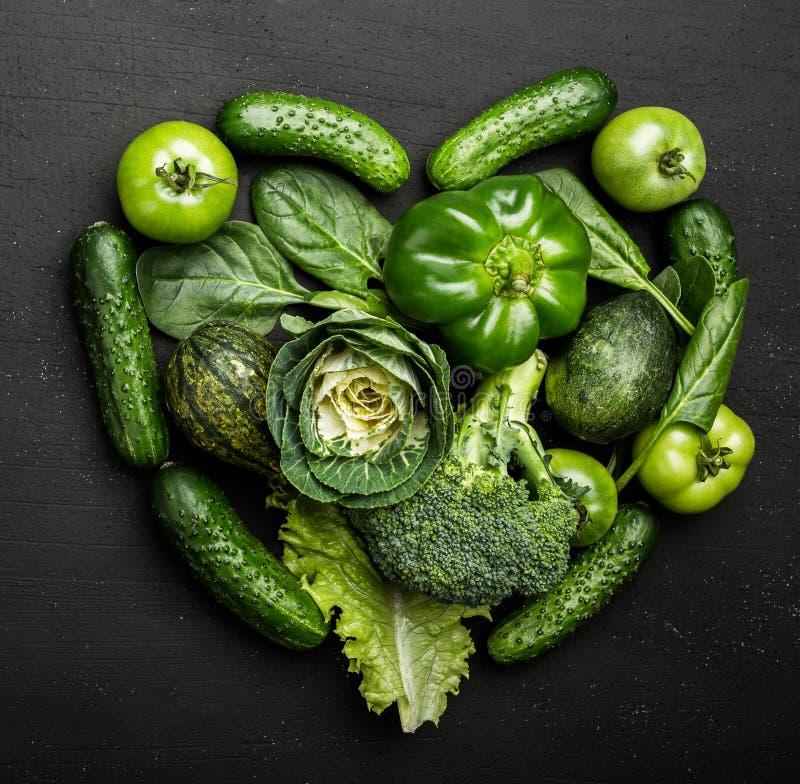 Zieleni warzywa układający w kierowym kształcie na wieśniaka kamienia stole Jarski pojęcie zdrowy łasowanie, odgórny widok fotografia royalty free