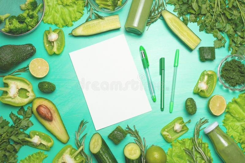 Zieleni warzywa z nutową książką dla inskrypcji Przygotowywać zdrowego i zdrowego posiłek Zdrowy zielony weganinu kucharstwo zdjęcia royalty free
