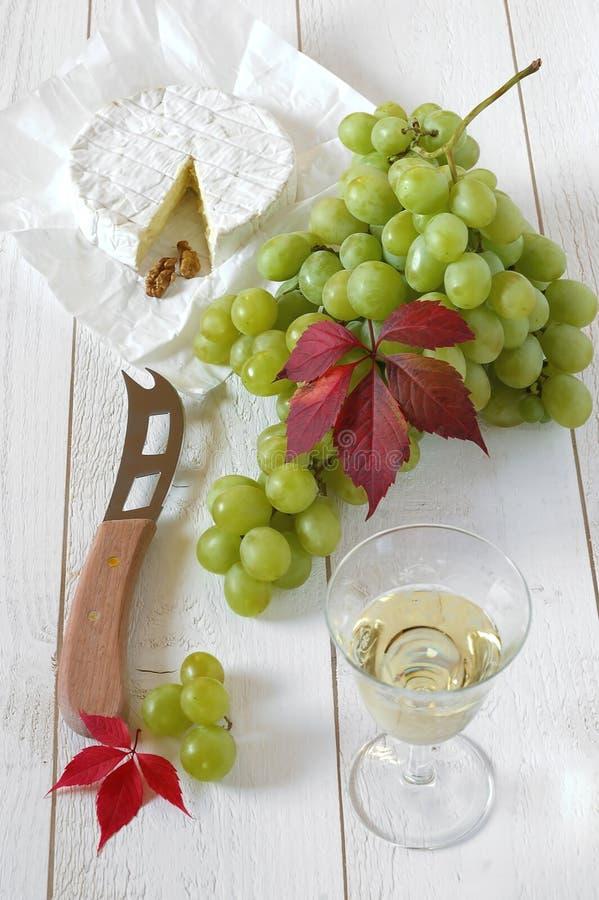 Zieleni winogrona, Francuski serowy Camembert i szkło biały wino, obraz stock