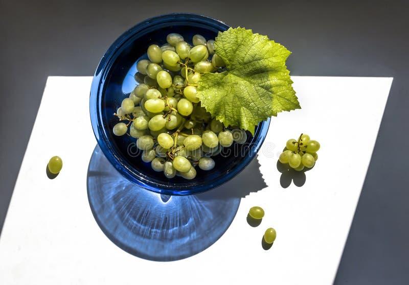 Zieleni winogrona w błękitnej szklanej wazie w słońce widoku od above fotografia stock
