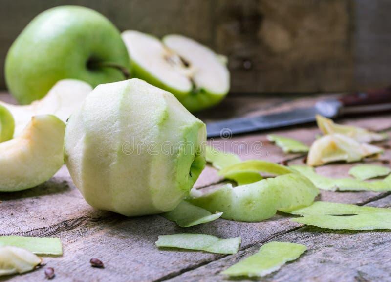 Zielenieje obranego jabłka na naturalnym nieociosanym drewnianym tle zdjęcie stock