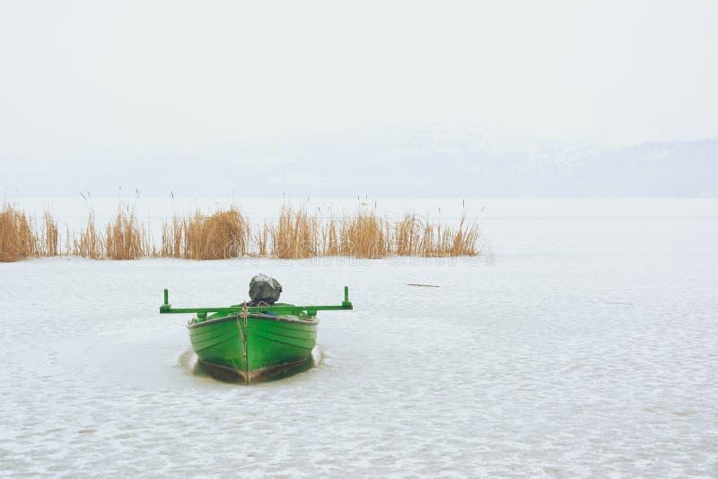 Zielona łódź łapać w pułapkę w zamarzniętym jeziorze obraz royalty free