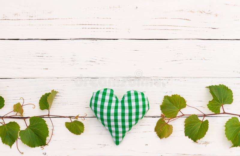 Zielona świeża winorośli granica, serce na nieociosanym białym drewnie i zgłaszamy tło obrazy stock
