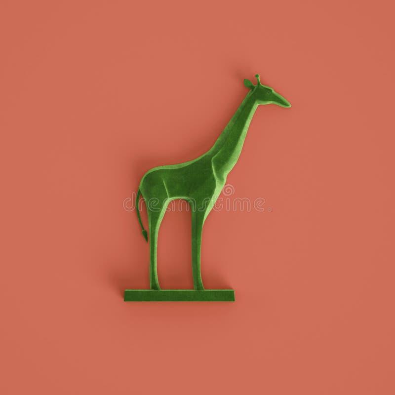 Zielona żyrafy rzeźba na pastelowym czerwonym tle ?wiadczenia 3 d obrazy stock