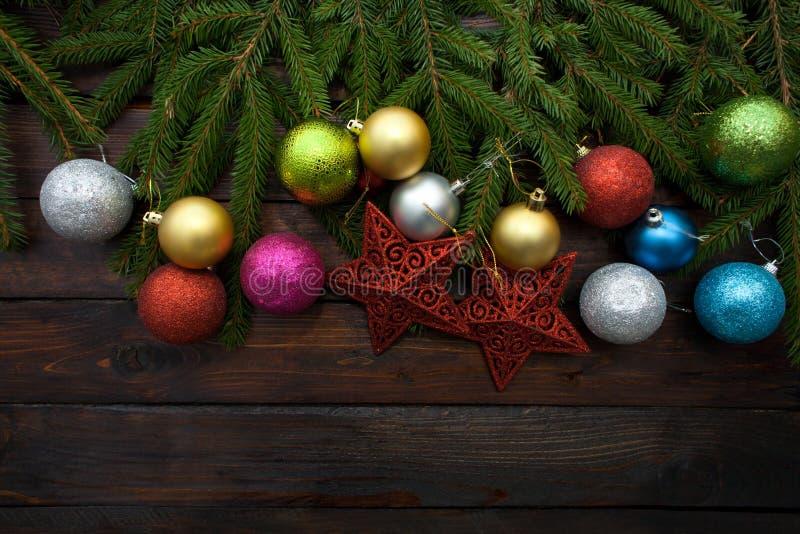 Zielona żywa świerczyna rozgałęzia się na ciemnym drewnianym tle Nowego Roku tło z czerwieni gwiazdami i kolorowymi piłkami Odgór zdjęcie stock