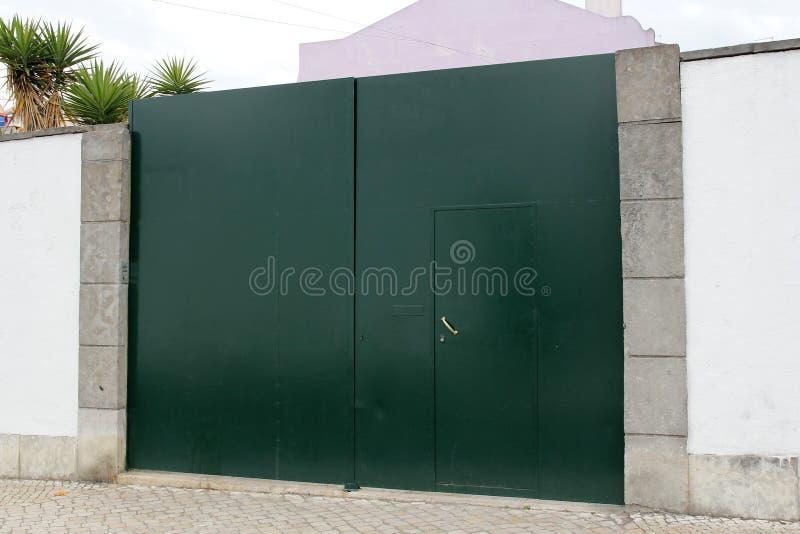 Zielona brama w biel ścianie fotografia stock