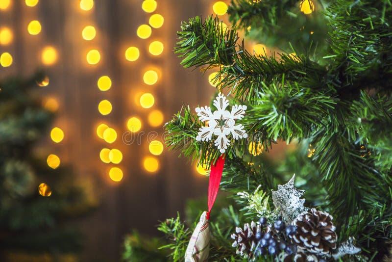 Zielona choinka dekorująca z boże narodzenie zabawkami i girlandą z żółtymi światłami fotografia stock