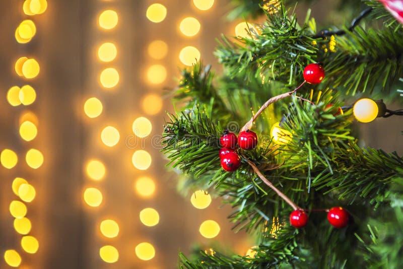 Zielona choinka dekorująca z boże narodzenie zabawkami i girlandą z żółtymi światłami zdjęcia stock