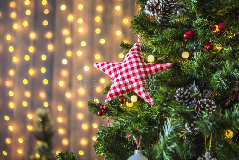 Zielona choinka dekorująca z boże narodzenie zabawkami i girlandą z żółtymi światłami zdjęcie stock