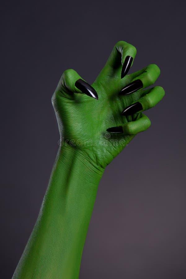 Zielona czarownicy ręka z ostrymi czarnymi gwoździami, istna sztuka fotografia stock