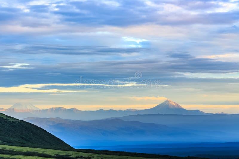 Zielona dolina zakrywająca z chmurami z dymień volcanoes w backg fotografia stock