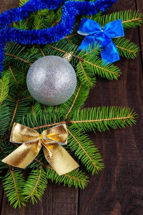 Zielona gałąź jodła, dekorująca z kolorowymi faborkami i srebną piłką na ciemnym drewnianym tle obrazy royalty free