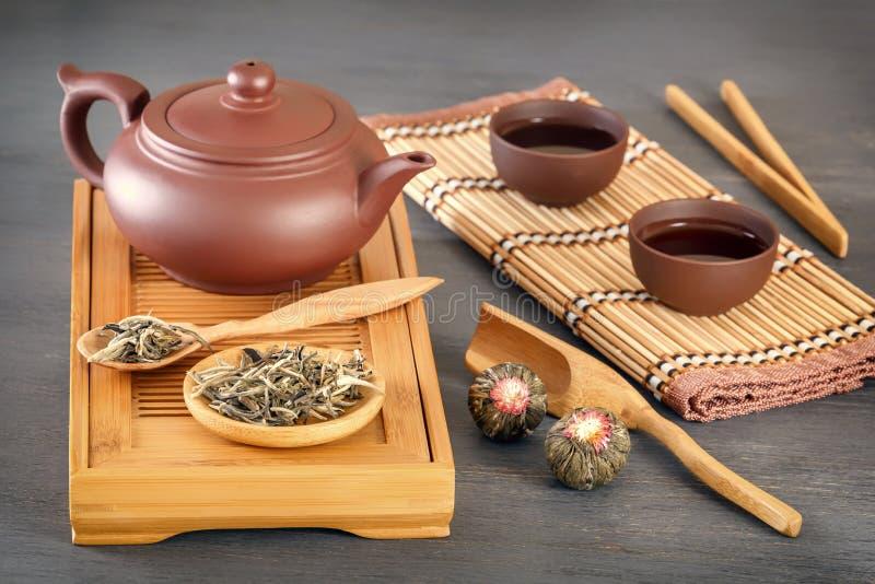 Zielona herbata i atrybuty dla herbacianej ceremonii ceramiczny teapot, filiżanki, durszlak, chopsticks i pincety -, zdjęcia royalty free