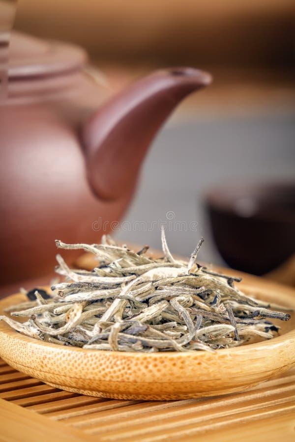 Zielona herbata i atrybuty dla herbacianej ceremonii - ceramiczny teapot, filiżanki, durszlak, chopsticks i pincety, umieszczamy obrazy royalty free
