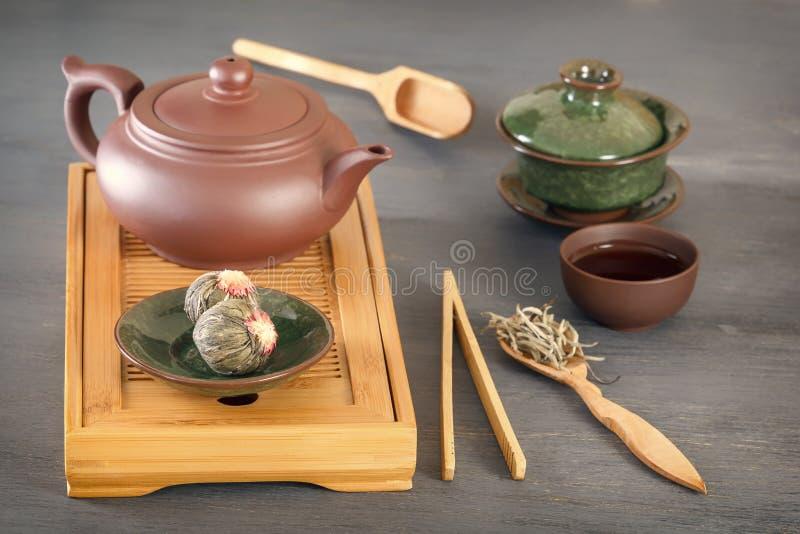 Zielona herbata pączki, ceramiczny teapot, filiżanki, drewniana herbaciana taca i inni atrybuty dla tradycyjnego herbacianego cer obraz royalty free