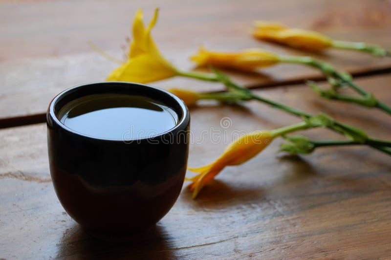 Zielona herbata puchar na ciemnego brązu drewnianym tle z pięknymi żółtymi lelujami zdjęcie royalty free