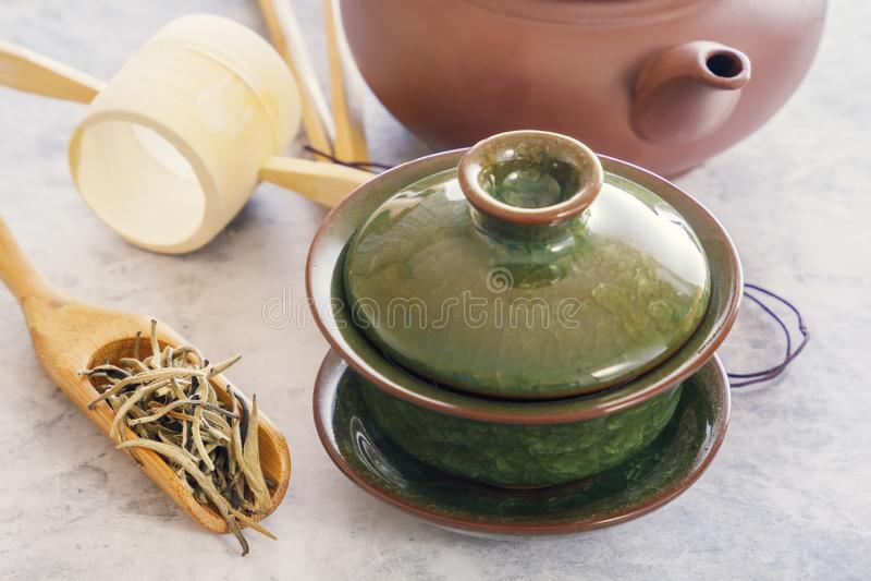 Zielona herbata w drewnianej łyżce, atrybuty dla herbacianej ceremonii i tradycyjni chińskie porcelana, zieleniejemy filiżankę zdjęcie royalty free