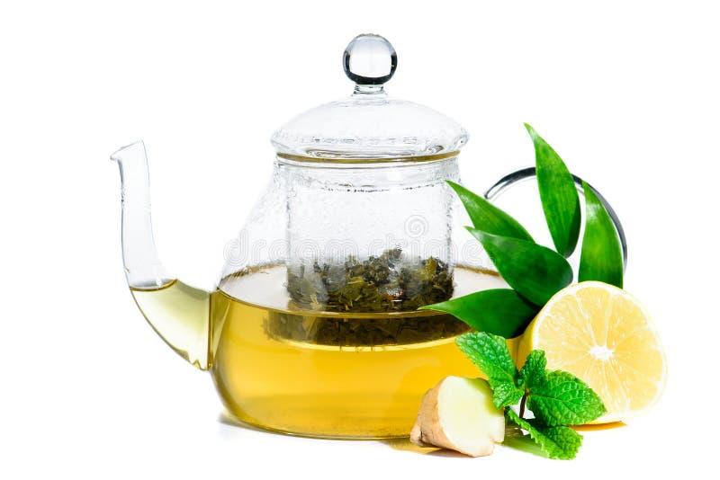 Zielona herbata z imbirem i mennicą z herbacianym liściem w szklanym teapot iso obraz stock