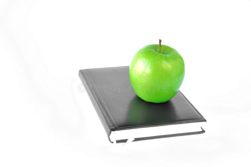 Zielona jabłczana pozycja na książce na białym tle lub notatniku fotografia royalty free