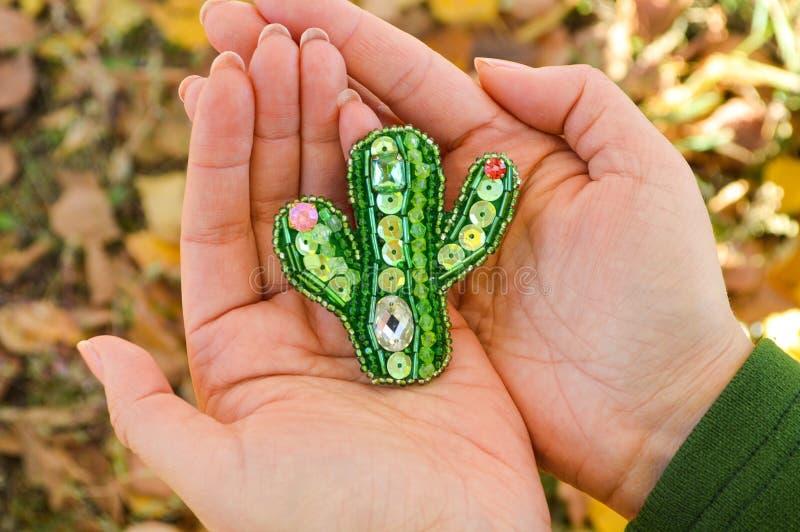 Zielona kaktus zabawka, handmade paciorkowata broszka, kłama na kobiet palmach Fotografuj?cy w Kuba fotografia stock