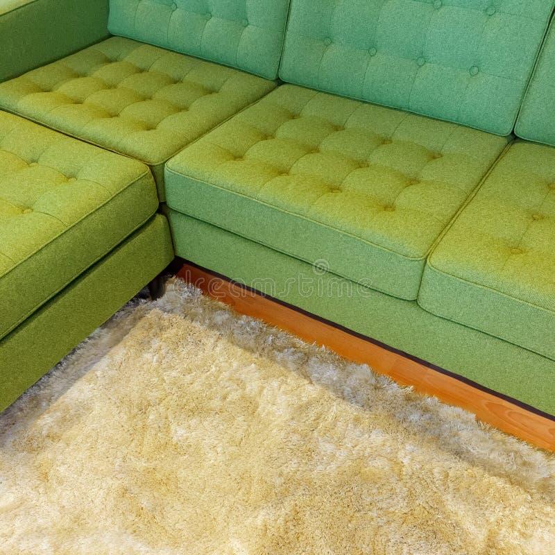 Zielona narożnikowa kanapa na puszystym dywaniku fotografia stock