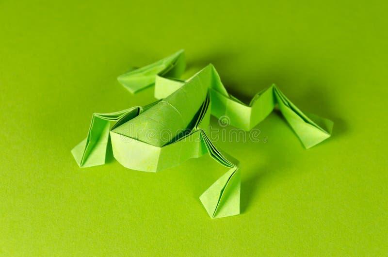 Zielona origami żaba na zielonym tle fotografia stock