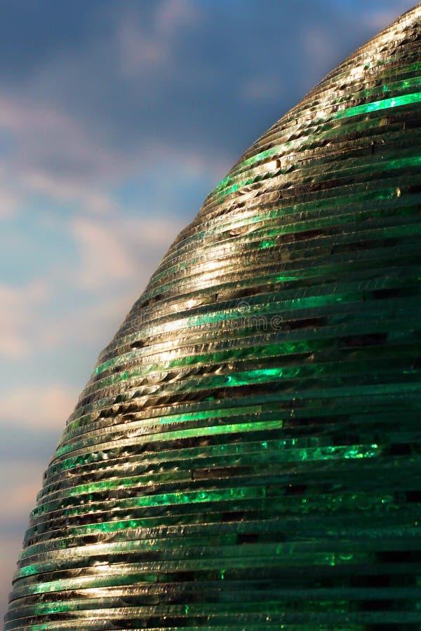 Zielona przejrzysta piłka robić szkło ciąć na arkusze przeciw niebieskiemu niebu zdjęcie stock