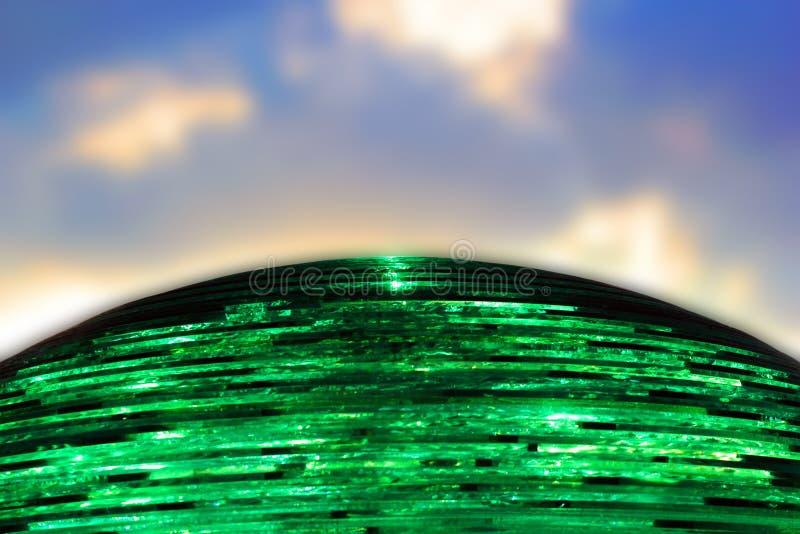 Zielona przejrzysta piłka robić szkło ciąć na arkusze przeciw słońcu i niebieskiemu niebu fotografia royalty free