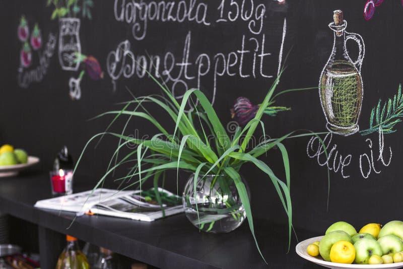 Zielona roślina w przejrzystej round wazie i talerzu owoc dalej obraz stock