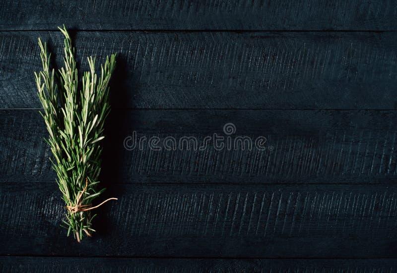 Zielona rozmarynowa wiązka na czarnego rocznika tła drewnianym zakończeniu w górę odgórnego widoku, naturalny organicznie aromaty fotografia stock