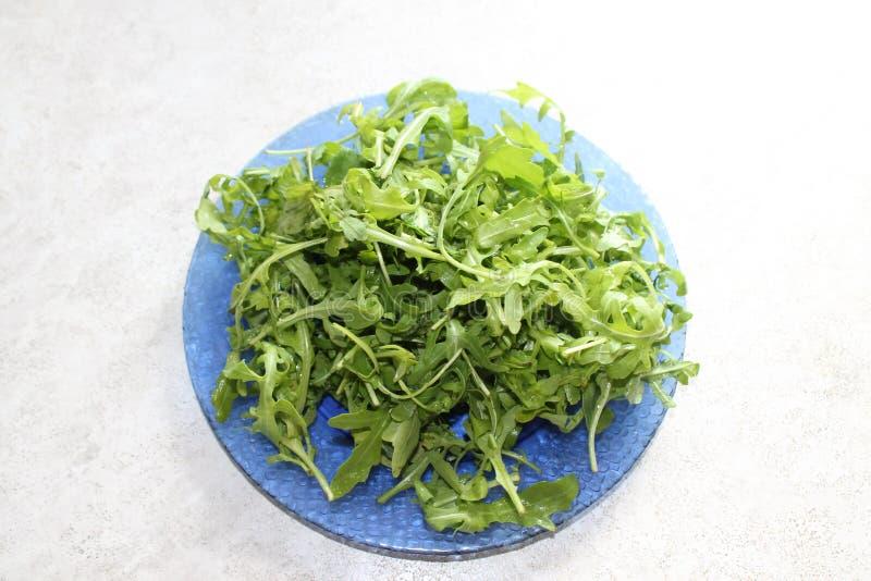 Zielona soczysta arugula sałatka na pięknym błękita talerzu obrazy stock