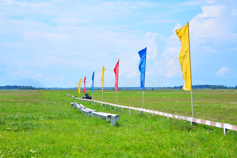 Zielona trawa na polu z niebieskim niebem i dodatek specjalny my fechtujemy si? z flagami r??ni kolory Lotniska pole Teren dla sp obraz stock