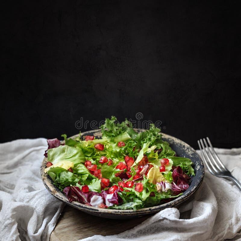 Zielona weganin sałatka w pucharze z endywią, arugula, mieszanymi sałatami i granatowem, fotografia royalty free