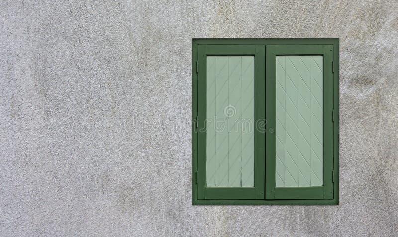 Zielone okna drewniane znajdują się na białej ścianie cementowej, gdzie można umieścić miejsce na tekst lub obraz obraz royalty free