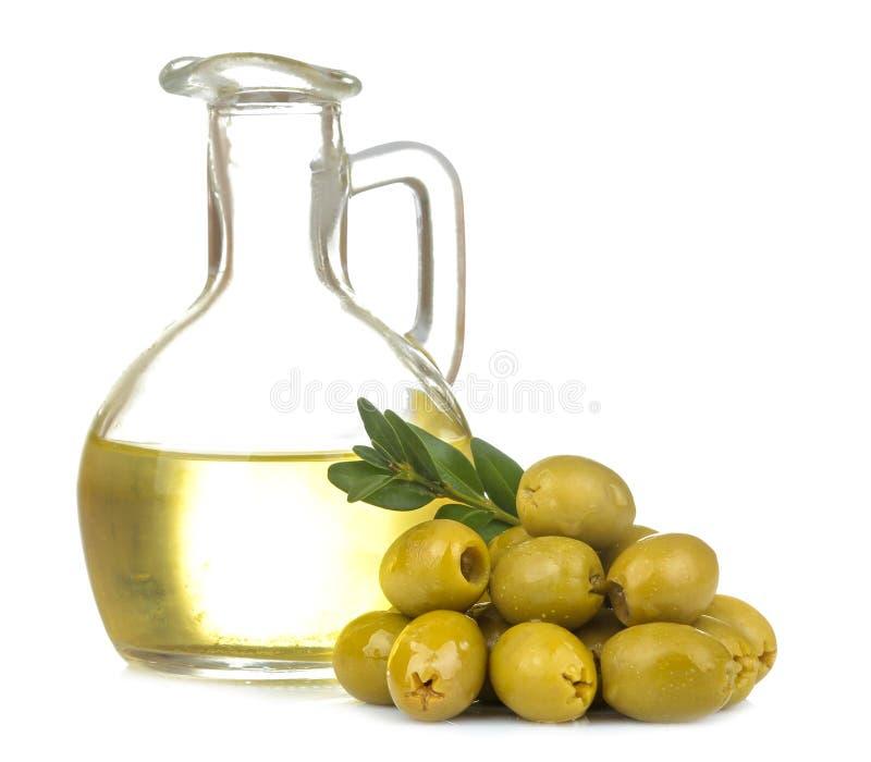 Zielone oliwki z oliwą z oliwek i liśćmi zamykają w górę białego odosobnionego tła dalej zdjęcia royalty free