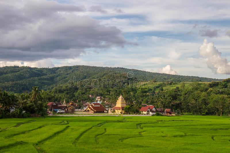 Zielone pole z Wat Sri Pho Chai, tło gór i niebieskie niebo na Haeo, Loei, Tajlandia zdjęcia stock